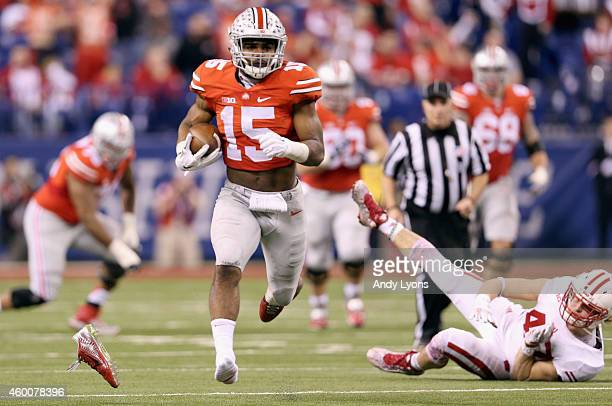 Ezekiel Elliott of the Ohio State Buckeyes loses his shoe as he runs with the ball in the fourth quarter of the Big Ten Championship against the...