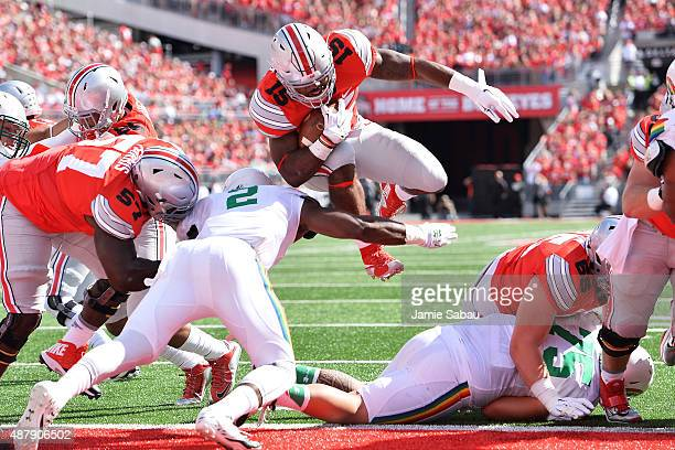Ezekiel Elliott of the Ohio State Buckeyes scores on a 1yard touchdown run past Jerrol GarciaWilliams of the Hawaii Rainbow Warriors in the first...