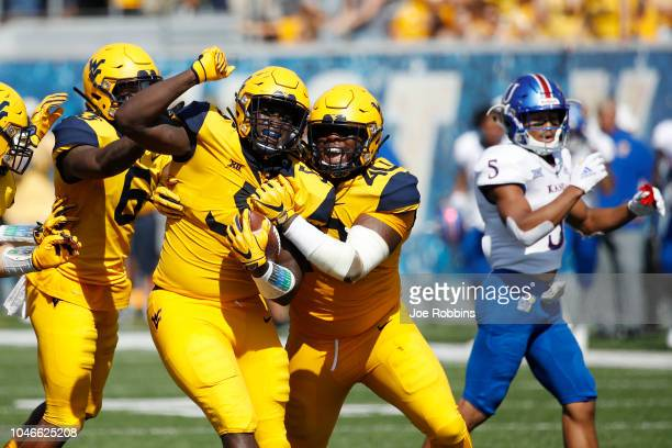 Ezekiel Rose of the West Virginia Mountaineers celebrates with teammates after an interception off a deflected pass against the Kansas Jayhawks in...