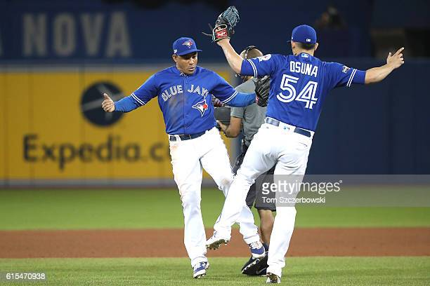 Ezequiel Carrera and Roberto Osuna of the Toronto Blue Jays celebrate after defeating the Cleveland Indians with a score of 5 to 1 in game four of...