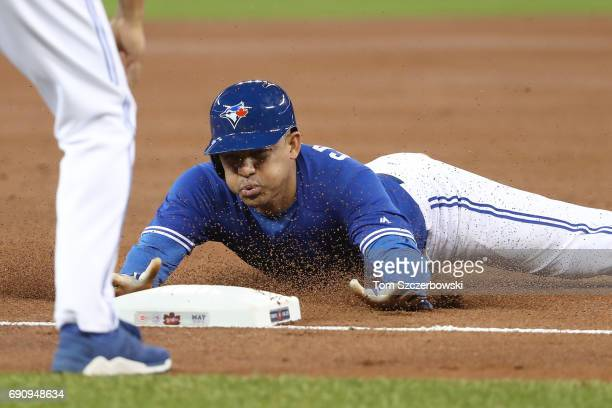 Ezequiel Carrera of the Toronto Blue Jays advances safely from first base to third base on a single as he slides in safely in the first inning during...