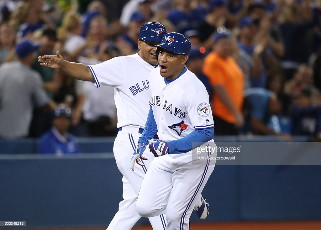 Ezequiel Carrera #3 of the Toronto Blue Jays celebrates as he is congratulated by third base coach Luis Rivera #2 after hitting a pinch-hit solo home run in the eighth inning during MLB game action against the Tampa Bay Rays on September 12, 2016 at Rogers Centre in Toronto, Ontario, Canada.