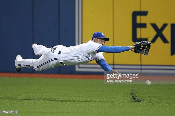 Ezequiel Carrera of the Toronto Blue Jays dives but cannot get to a single hit by Jett Bandy of the Los Angeles Angels of Anaheim in the seventh...