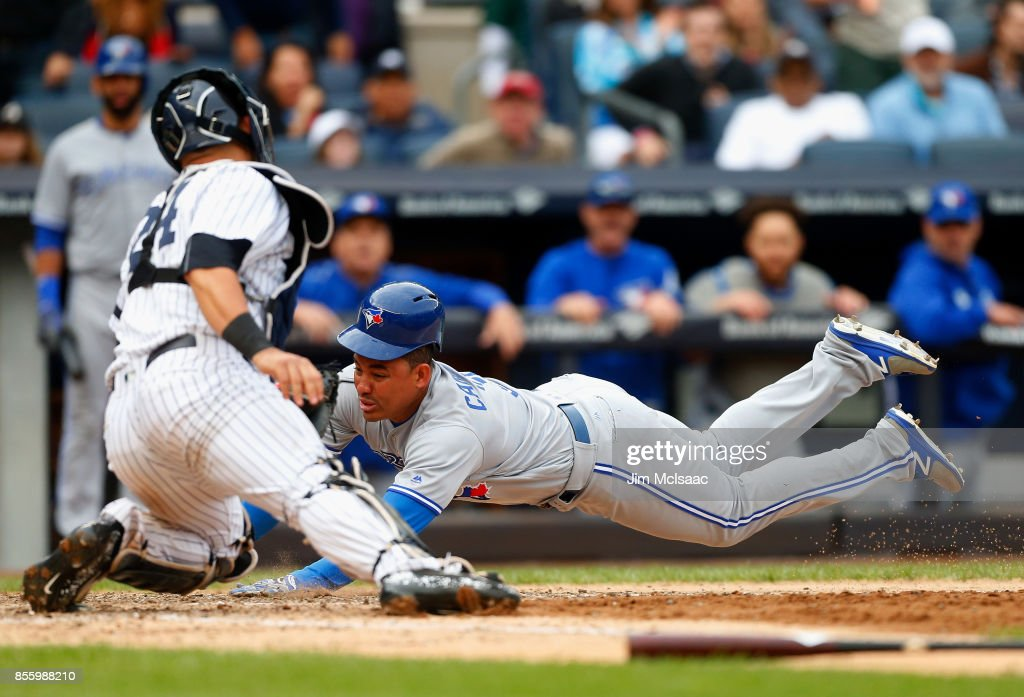 Ezequiel Carrera #3 of the Toronto Blue Jays dives home for a run in the eighth inning against Gary Sanchez #24 of the New York Yankees at Yankee Stadium on September 30, 2017 in the Bronx borough of New York City.
