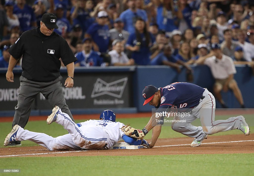 Ezequiel Carrera #3 of the Toronto Blue Jays gets back safely to third base as Eduardo Escobar #5 of the Minnesota Twins tries to tag him out in the sixth inning during MLB game action on August 26, 2016 at Rogers Centre in Toronto, Ontario, Canada.