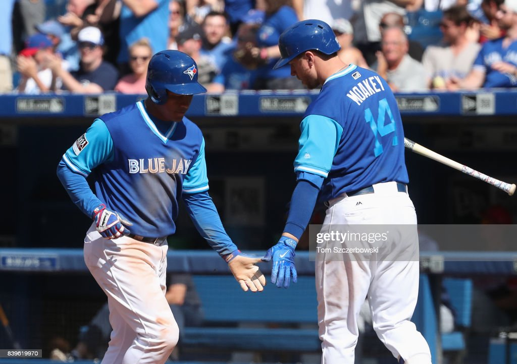 Ezequiel Carrera #3 of the Toronto Blue Jays is congratulated by Justin Smoak #14 after scoring a run in the eighth inning during MLB game action against the Minnesota Twins at Rogers Centre on August 26, 2017 in Toronto, Canada.