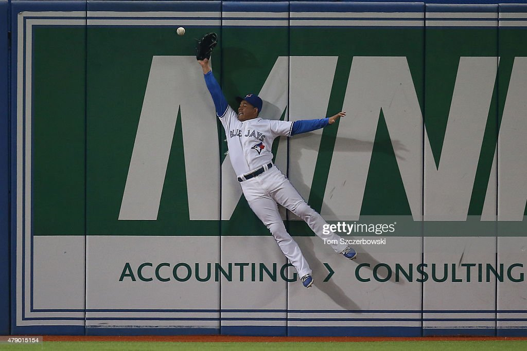 Ezequiel Carrera #3 of the Toronto Blue Jays jumps but cannot get to a ball that went for a triple in the ninth inning off the bat of Alejandro De Aza of the Boston Red Sox on June 29, 2015 at Rogers Centre in Toronto, Ontario, Canada.
