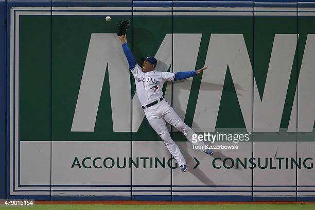 Ezequiel Carrera of the Toronto Blue Jays jumps but cannot get to a ball that went for a triple in the ninth inning off the bat of Alejandro De Aza...