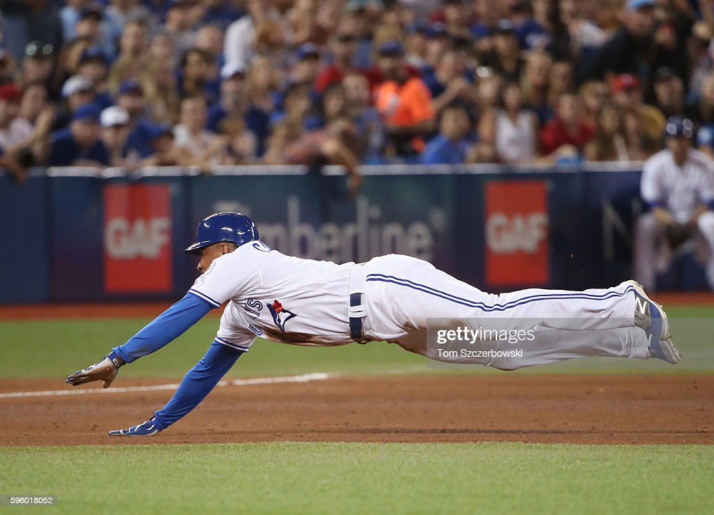 Ezequiel Carrera #3 of the Toronto Blue Jays slides into third base as he advances on a throwing error in the sixth inning during MLB game action against the Minnesota Twins on August 26, 2016 at Rogers Centre in Toronto, Ontario, Canada.
