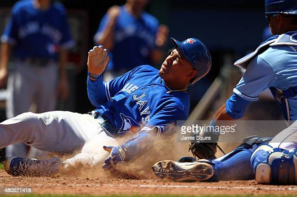 Ezequiel Carrera of the Toronto Blue Jays slides safely into home plate to score as Salvador Perez of the Kansas City Royals misses him with the tag...