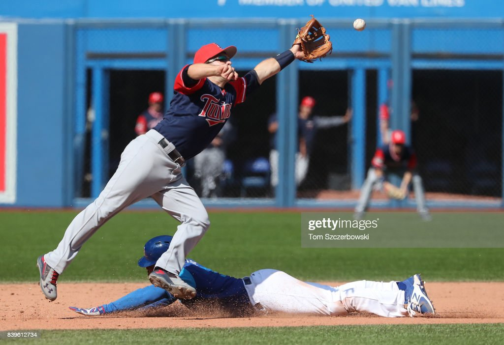 Ezequiel Carrera #3 of the Toronto Blue Jays steals second base in the eighth inning during MLB game action as Brian Dozier #2 of the Minnesota Twins reaches for the ball on a throwing error by Mitch Garver #43 at Rogers Centre on August 26, 2017 in Toronto, Canada.