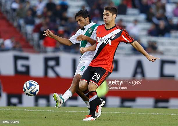 Ezequiel Cirigliano of River Plate fights for the ball with Walter Erviti of Banfield during a match between Banfield and River Plate as part of...