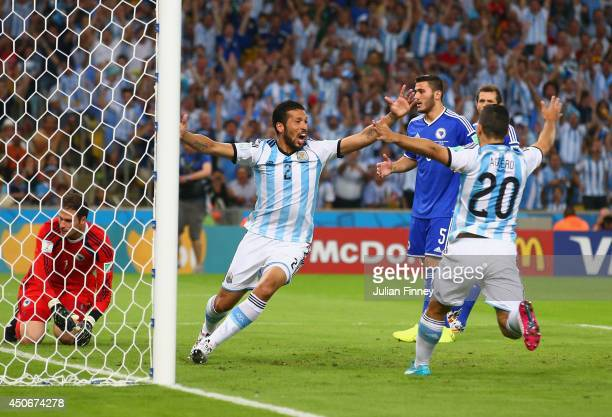 Ezequiel Garay and Sergio Aguero of Argentina celebrate their team's first goal an own goal off Sead Kolasinac of Bosnia and Herzegovina past...