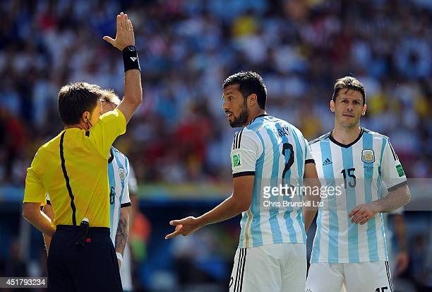 Ezequiel Garay of Argentina appeals to referee Nicola Rizzoli during the 2014 FIFA World Cup Brazil Quarter Final match between Argentina and Belgium...