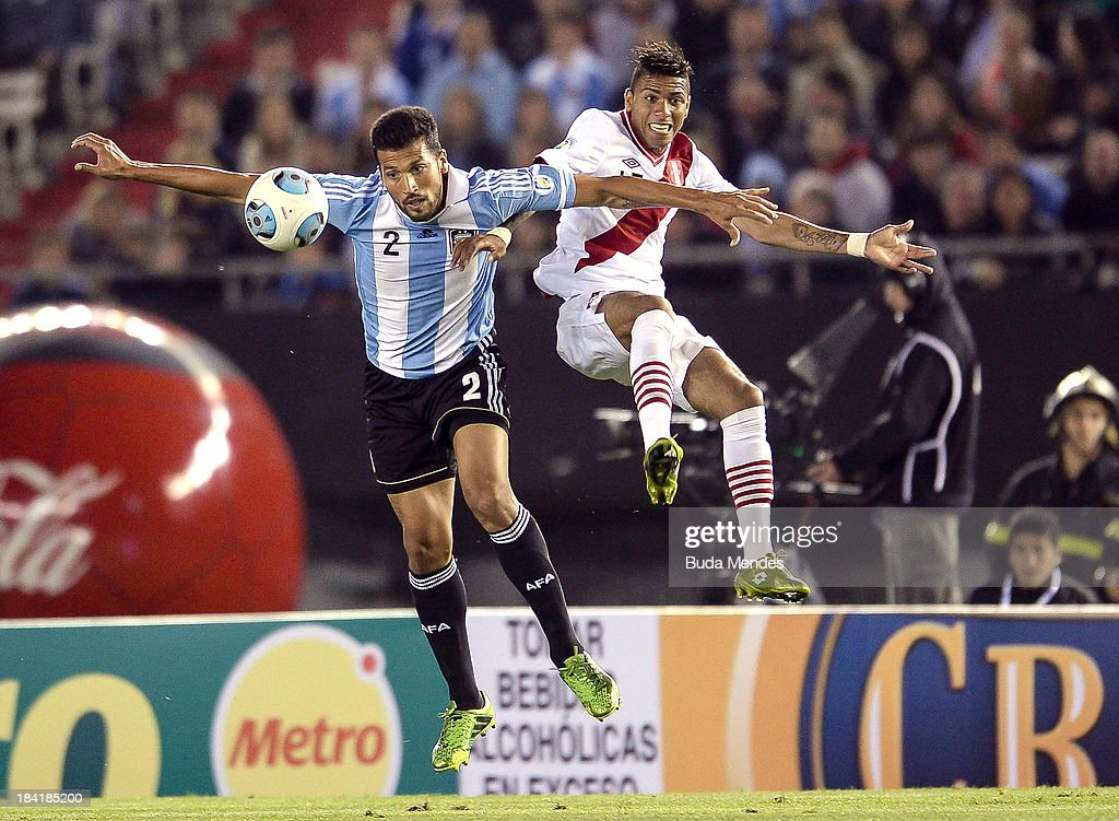 Ezequiel Garay (L) of Argentina fights for the ball with Edwuin Gomez Gutierrez of Peru during a match between Argentina and Peru as part of the 17th round of the South American Qualifiers for the FIFA's World Cup Brazil 2014 at Antonio Vespucio Liberti Stadium on October 11, 2013 in Buenos Aires, Argentina.