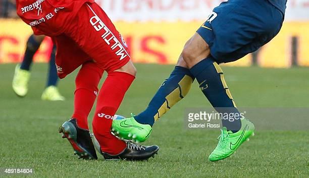 Ezequiel Ham of Argentinos Juniors is fouled and injured by Carlos Tevez of Boca Juniors during a match between Argentinos Juniors and Boca Juniors...