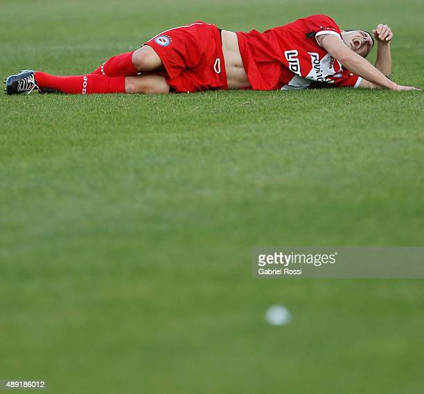 Ezequiel Ham of Argentinos Juniors lies injuried after receiving a foul from Carlos Tevez of Boca Juniors during a match between Argentinos Juniors...