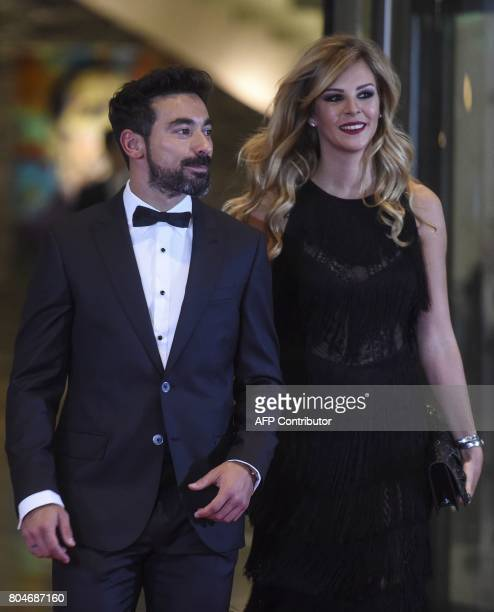 Ezequiel Lavezzi and his wife pose on a red carpet upon arrival to attend Argentine football star Lionel Messi and Antonella Roccuzzo's wedding in...