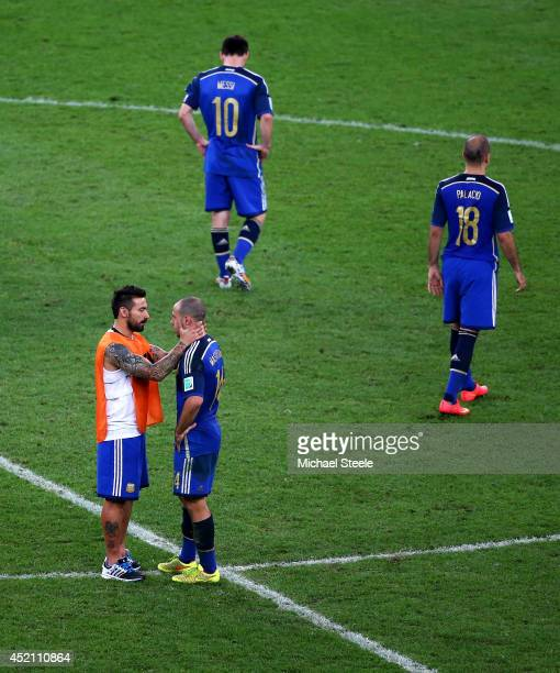Ezequiel Lavezzi of Argentina consoles teammate Javier Mascherano as Lionel Messi and Rodrigo Palacio look on after being defeated by Germany 10 in...