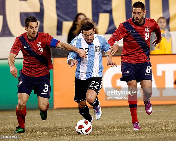 Ezequiel Lavezzi of Argentina dribbles between Carlos Bocanegra and Clint Dempsey of the United States during the first half of a friendly match at...
