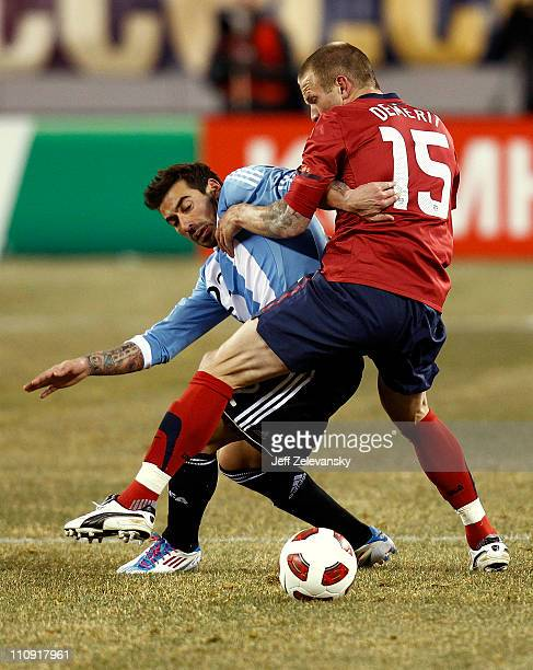 Ezequiel Lavezzi of Argentina fights for the ball with Jay DeMerit of the United States during the first half of a friendly match at New Meadowlands...