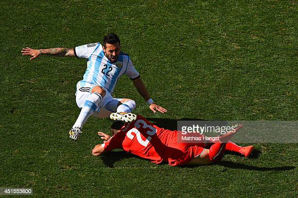 Ezequiel Lavezzi of Argentina is challenged by Xherdan Shaqiri of Switzerland during the 2014 FIFA World Cup Brazil Round of 16 match between...