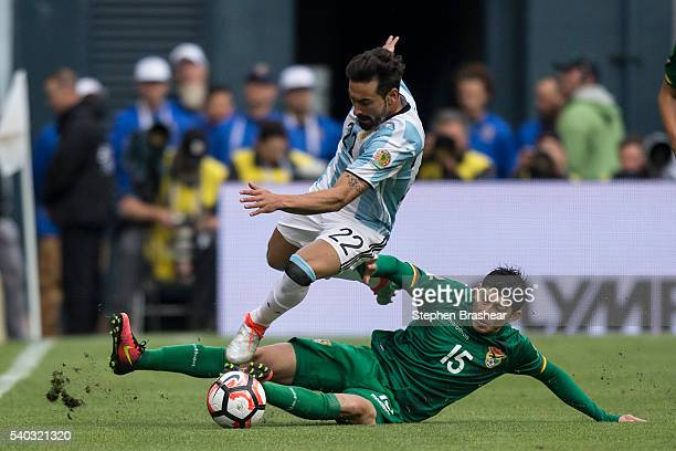 Ezequiel Lavezzi of Argentina tries to avoid the defensive slide by Pedro Azogue of Bolivia during a group D match between Argentina and Bolivia at...