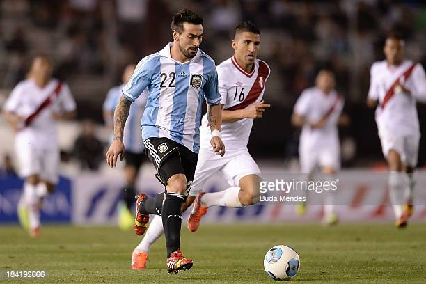 Ezequiel Lavezzi of Argentina vies for the ball with Josepmir Ballon of Peru during a match between Argentina and Peru as part of the 17th round of...