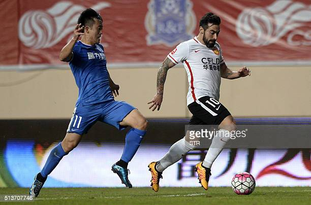 Ezequiel Lavezzi of Hebei CFFC dribbles the ball past Jiang Zhipeng of Guangzhou RF during their Chinese Super League football match in Guangzhou on...