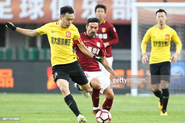 Ezequiel Lavezzi of Hebei China Fortune and Feng Xiaoting of Guangzhou Evergrande compete for the ball during the Chinese Super League match between...