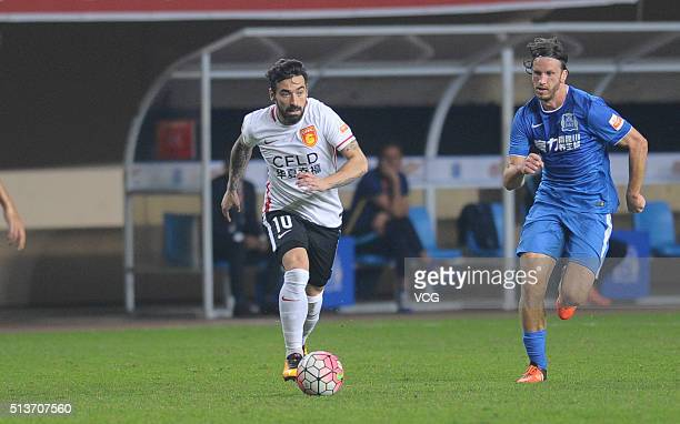 Ezequiel Lavezzi of Hebei China Fortune and Gustav Svensson of Guangzhou RF compete for the ball during the Chinese Football Association Super League...