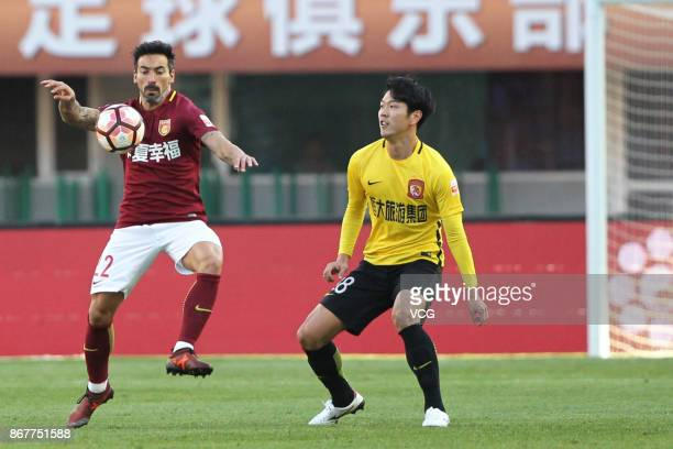 Ezequiel Lavezzi of Hebei China Fortune and Kim YoungKwon of Guangzhou Evergrande compete for the ball during the Chinese Super League match between...