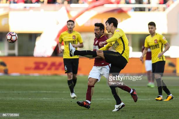 Ezequiel Lavezzi of Hebei China Fortune crashes with Kim YoungGwon of Guangzhou Evergrande during the Chinese Super League match between Hebei China...