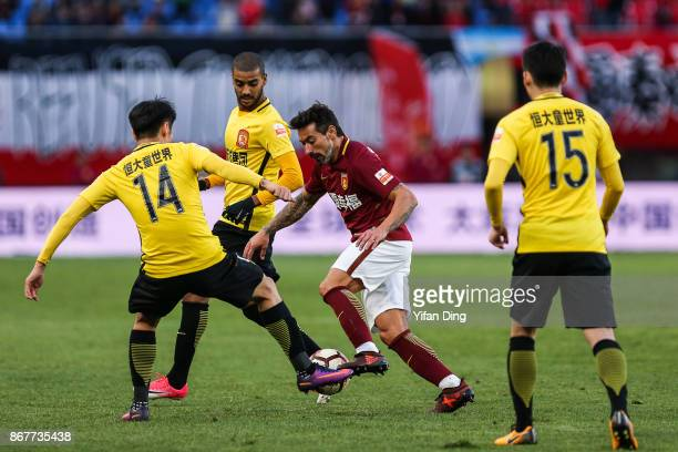 Ezequiel Lavezzi of Hebei China Fortune dribbles past Rong Hao of Guangzhou Evergrande during the Chinese Super League match between Hebei China...