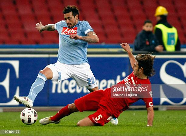 Ezequiel Lavezzi of Napoli is tackled by Daniele Conti of Cagliari during the Serie A match between SSC Napoli and Cagliari Calcio at Stadio San...