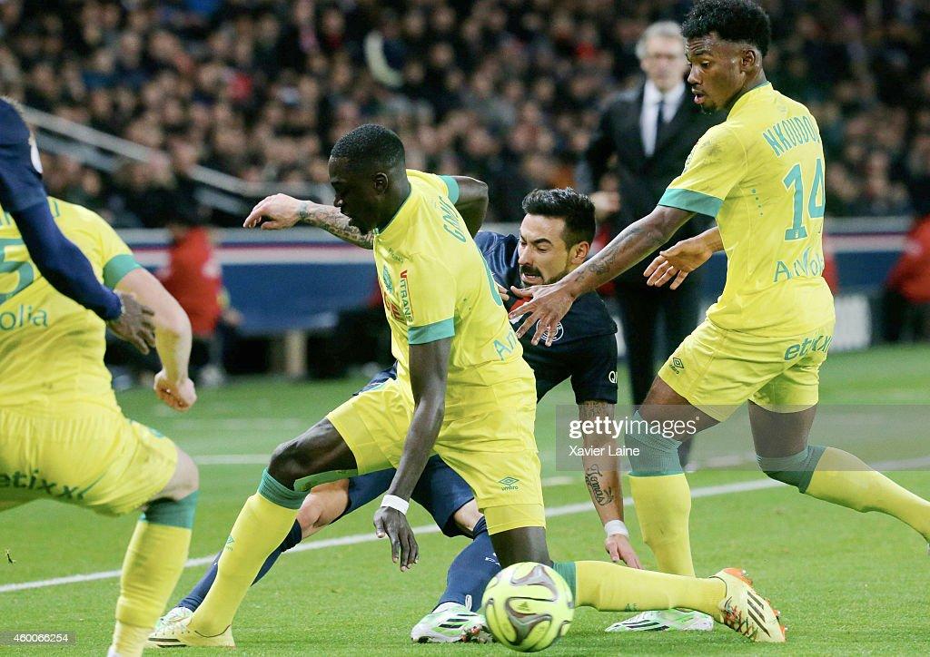 Ezequiel Lavezzi of Paris Saint-Germain is caught by Remy Gomis and Kevin Nkoudou of FC Nantes during the French Ligue 1 between Paris Saint-Germain FC and FC Nantes at Parc Des Princes on December 06, 2014 in Paris, France.