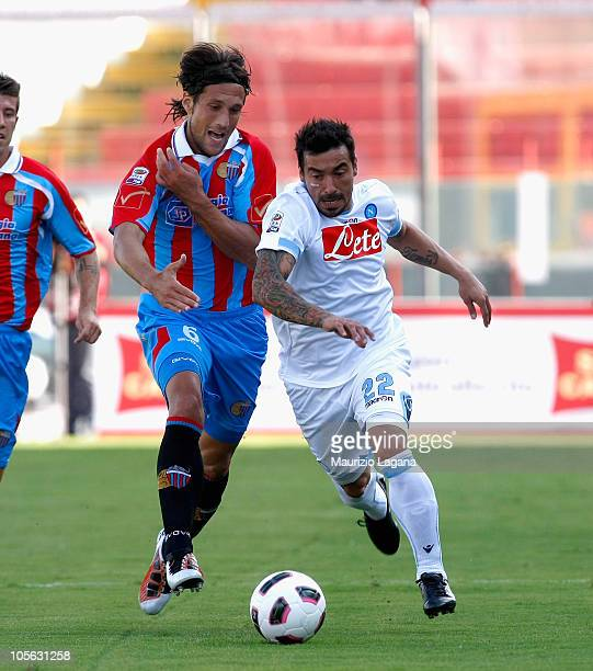 Ezequiel Lavezzi of SSC Napoli is challenged by Matias Silvestre during the Serie A match between Catania Calcio and SSC Napoli at Stadio Angelo...