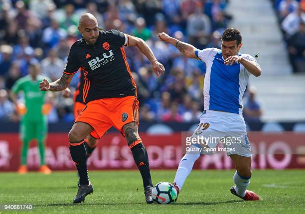 Ezequiel Munoz of Leganes competes for the ball with Simone Zaza of Valencia during the La Liga match between Leganes and Valencia at Estadio...