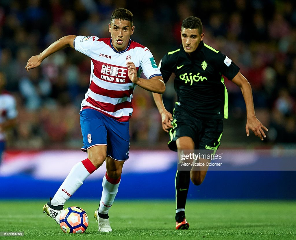 Ezequiel Ponce of Granada CF (L) being followed by Rachid Ait-Atmane of Sporting Gijon during the match between Granada CF vs Sporting Gijon as part of La Liga at Nuevo los Carmenes Stadium on October 22, 2016 in Granada, Spain.