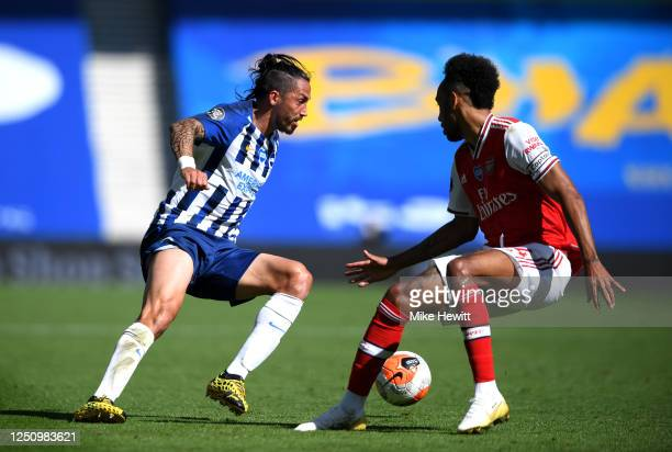 Ezequiel Schelotto of Brighton and Hove Albion is challenged by PierreEmerick Aubameyang of Arsenal during the Premier League match between Brighton...