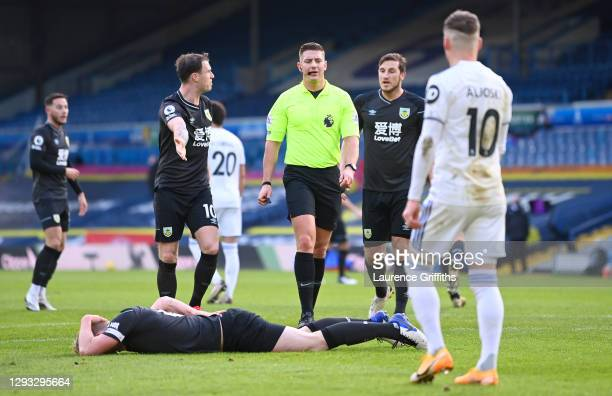 Ezgjan Alioski of Leeds United protests to the referee Robert Jones as Ben Mee of Burnley is seen injured after a foul during the Premier League...