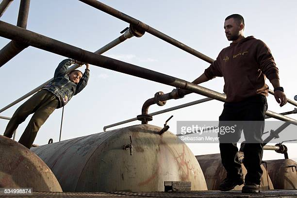 Ezidiar watches his brother Zaidoon check the valves on the machinery at the refinery The family of Yezidis displaced from Sinjar live next to an oil...