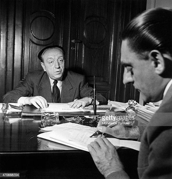 'MB Ezio Vanoni sitting at the writing desk of his office issues an interview to a journalist who is taking notes in the closeup Rome Fifties '