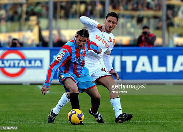 Ezquiel Carboni of Catania competes with Francesco Totti of Roma during the Serie A match between Catania and Roma at the Stadio Massimino on...