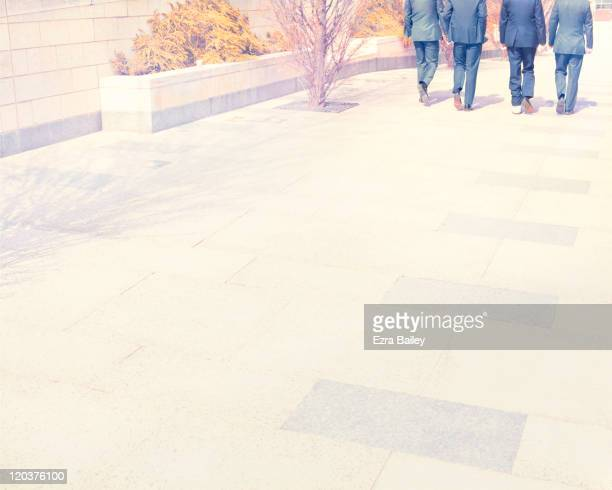 4 men in suits walking - newpremiumuk stock pictures, royalty-free photos & images
