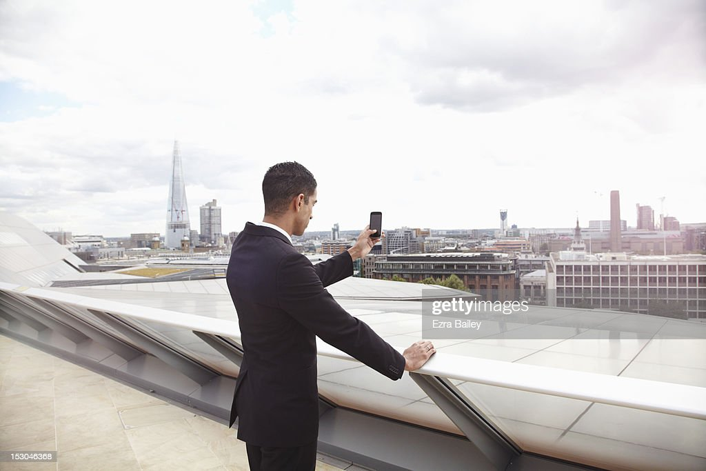 Businessman taking a photo of the city. : Stock Photo