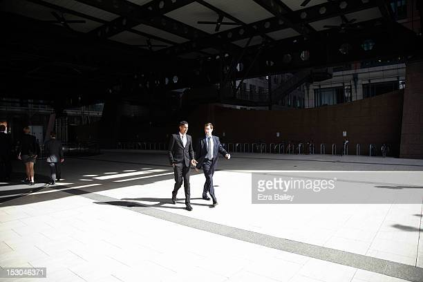 Two businessmen walking and talking.
