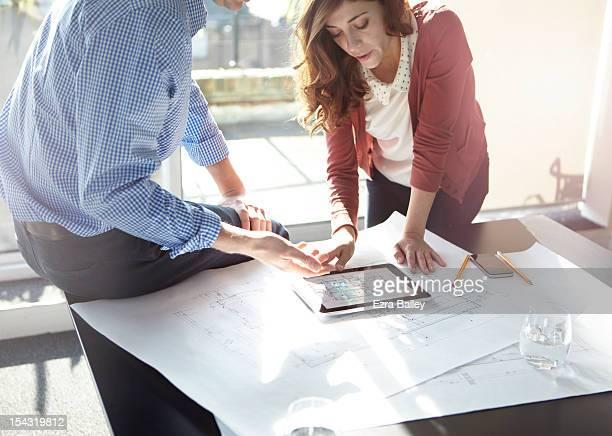 business people discussing plans on tablet. - architecte photos et images de collection