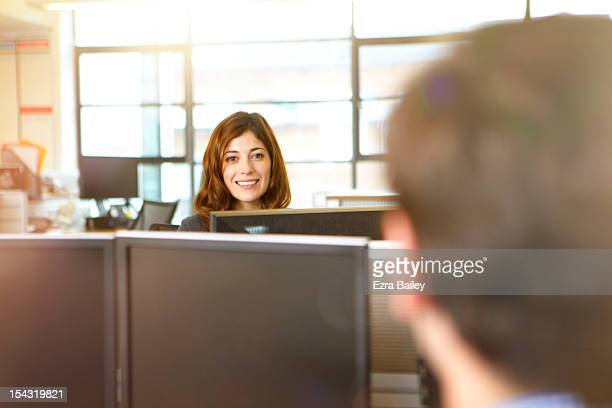 Business people chatting in open plan office.