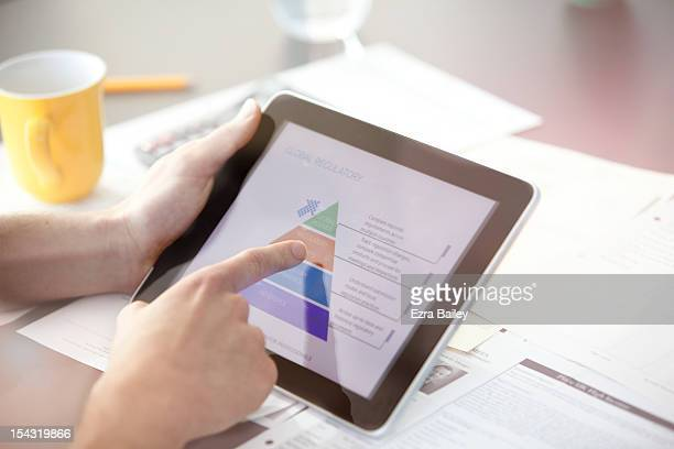 Man using a digital tablet with paperwork.